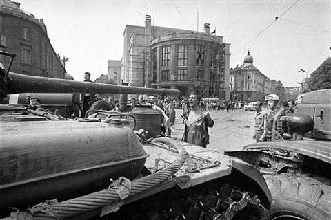 Muž s odhalenou hruďou pred okupačným tankom.